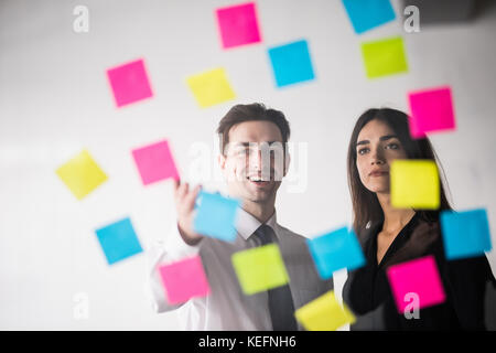 Démarrer la planification des activités et décisions de l'organisation jeune couple à l'intérieur de bureaux modernes Banque D'Images