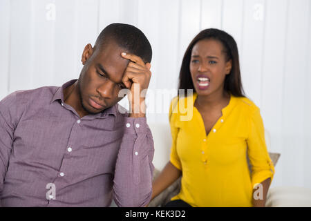 Jeune femme malheureuse having argument avec l'homme à la maison Banque D'Images