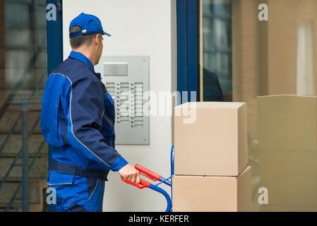 Delivery man avec chariot plein de boîte à l'aide de sécurité entrez dans l'édifice Banque D'Images