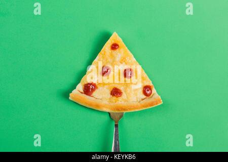 Tranche de pizza sur une fourche sur un fond vert Banque D'Images