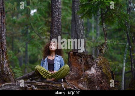 Jeune femme se reposant dans une forêt assis en méditation la posture appuyé contre un tronc d'arbre dans le magnifique Banque D'Images