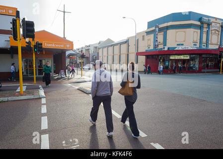 Un homme et une femmes utilisent le passage pour piétons à l'angle des rues d'Oxford et Vincent à Leederville, Perth, Banque D'Images