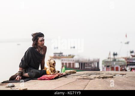 Un agori-yogi (hindou dévot) assis avec ses crânes humains à côté de la sainte gange et prier dans le lever du soleil. Banque D'Images
