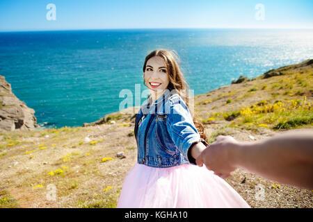 Beautiful woman smiling and holding l'homme par la main et aller au lac dans les montagnes au lever du soleil rougeoyant Banque D'Images