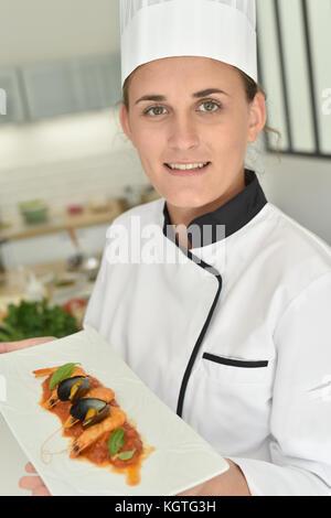 Jeune chef en cuisine Présentation de l'école de formation lave Banque D'Images