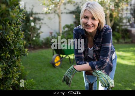 Portrait de femme belle appuyée sur l'équipement de jardinage Banque D'Images