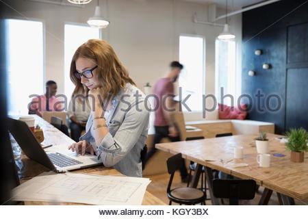 L'accent female architect with blueprints in espace de coworking Banque D'Images
