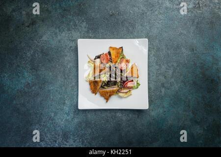 Pan-asiatique, salade de légumes avec poulet frit. sur une plaque carrée blanche. vue d'en haut. Banque D'Images