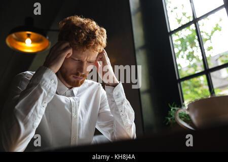 Close-up portrait of young man readhead surchargés de barbus en chemise blanche de toucher sa tête alors qu'il était Banque D'Images
