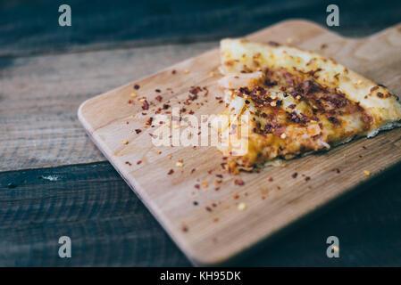 Pizza slice avec fromage, viande de poulet et d'ananas garniture sur une planche en bois/table.cuisine italienne Banque D'Images