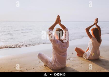 La méditation de groupe, yoga sur la plage au coucher du soleil Banque D'Images