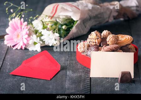 Félicitations thème image avec un papier vierge remarque s'appuya contre une boîte remplie de bonbons, entouré par Banque D'Images