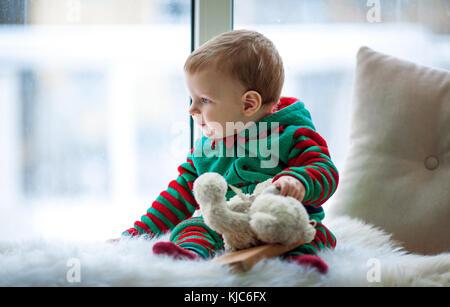 Petit garçon avec ours en peluche dans ses mains est assis sur un tapis de fourrure blanche et regarde par la fenêtre. Banque D'Images