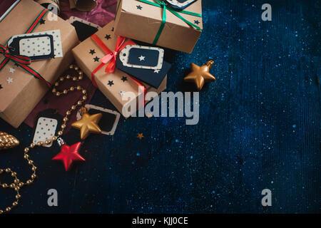 Décorations et gifts concept. fête de Noël dark flat fixer avec des boîtes en papier craft, étoiles, tags, de guirlandes Banque D'Images
