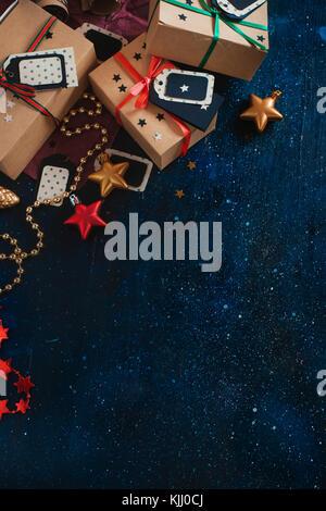 Décorations du nouvel an et gifts concept. fête de Noël dark flat fixer avec des boîtes en papier craft, étoiles, Banque D'Images