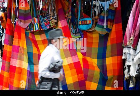 Marché d'Otavalo Équateur - un indigène passant un blocage des textiles colorés, Otavalo, Equateur, Amérique Latine Banque D'Images