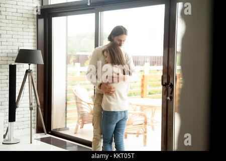 Young man and woman hugging debout à la maison, couple de réconciliation Banque D'Images