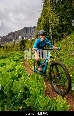 Femme biker smiling while riding descente sur sentier des lacs de glace, Colorado, USA Banque D'Images