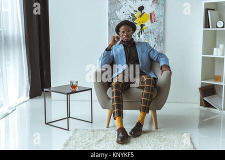 Homme élégant sitting in armchair Banque D'Images