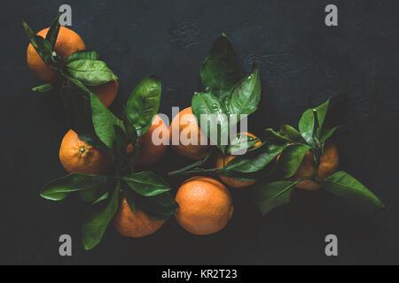 Mandarine avec des feuilles vertes sur fond sombre. Vue de dessus, image, moody still life Banque D'Images