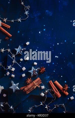 Mise à plat de Noël avec de l'argent jouets, décorations, la cannelle, l'anis étoile et marshmallow sur un fond Banque D'Images