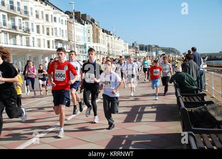 Les jeunes prennent part à un mini-courir le long du bord de mer à Hastings, East Sussex, Angleterre le 15 mars Banque D'Images