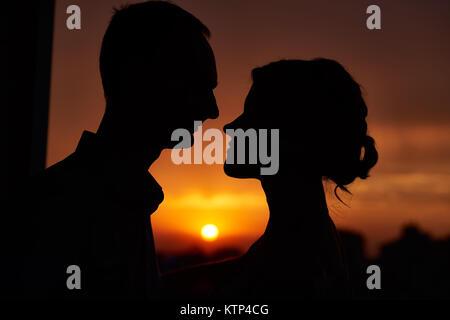 Close up chefs de deux amoureux silhouettes contre le coucher du soleil Banque D'Images