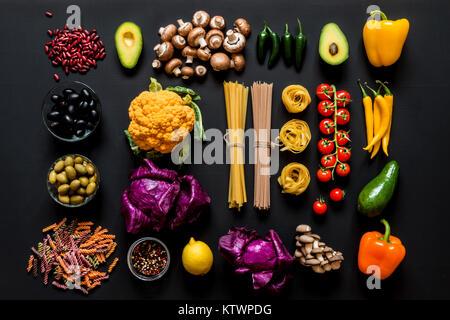 Différents ingrédients crus frais colorés pour la cuisine végétarienne saine sur un fond noir. Mise à plat, vue Banque D'Images