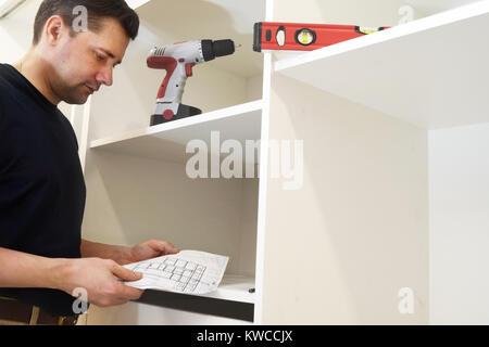 Man reading instructions d'installation pour armoire. Assemblage de meubles. Banque D'Images