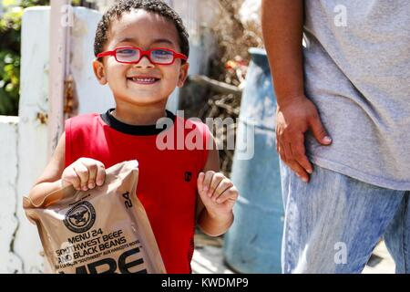 Un petit garçon avec des rations de l'armée de terre distribués à San Juan, Puerto Rico, après l'Ouragan Maria. Banque D'Images