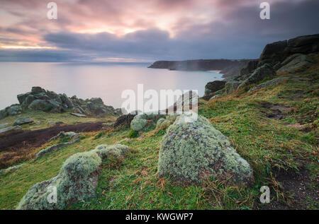 Coucher du soleil sur les falaises en direction de Porthcurno Treen Banque D'Images