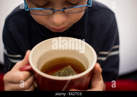 Un jeune garçon boit dans une tasse de thé dans une tasse rouge. Banque D'Images