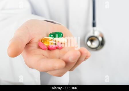 Plusieurs médicaments différents comprimés dans la main d'un médecin détenant un stéthoscope Banque D'Images
