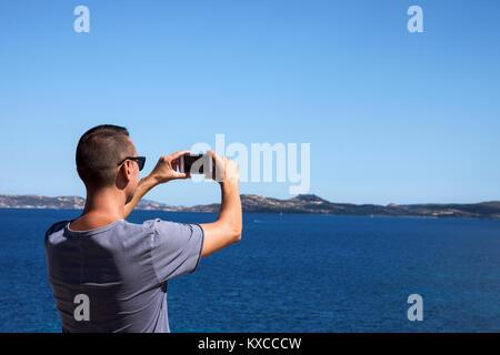 Libre d'un jeune homme de race blanche vue de derrière en prenant une photo de la mer sur la Costa Smeralda, en Banque D'Images