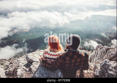 Couple Homme et Femme assise hugging on cliff profiter de montagnes et nuages amour paysage avec une assurance vie Banque D'Images