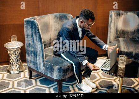 Le port de l'employé suit working on laptop en ligne Banque D'Images
