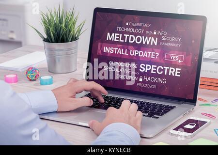 L'installation de la mise à jour contre meltdown et spectre menace sur l'ordinateur portable dans l'espace de bureau. Banque D'Images