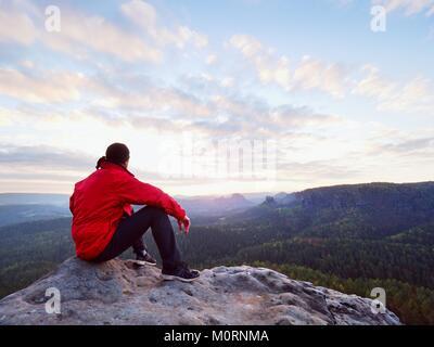 Hiker homme prendre un repos sur la montagne. Le poser sur l'homme, sommet de la vallée d'automne ci-dessous. Soleil Banque D'Images