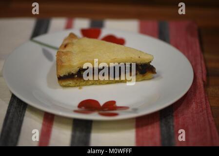 La photographie culinaire avec pâtisseries et fruits en cours de coupe sur une tarte Eccles anglaise rouge et blanc Banque D'Images