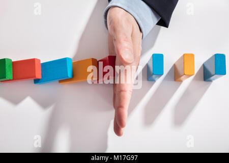 Portrait de l'homme d'affaires l'arrêt dominos colorés de tomber sur 24 Banque D'Images