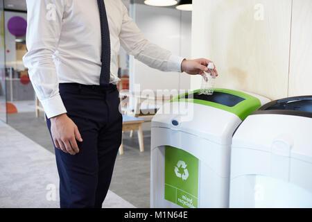 L'homme dans un bureau de jeter en bouteille de plastique bac de recyclage Banque D'Images