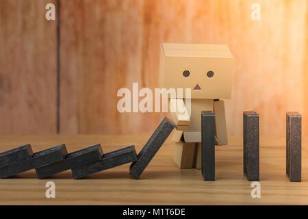 Effet Dominos Business Concept: poupée en papier d'arrêter ou arrêter la chute de l'effet domino renverser continue Banque D'Images