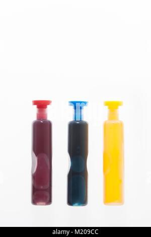 Trois conteneurs de rouge, bleu et jaune liquide, studio shot. Banque D'Images