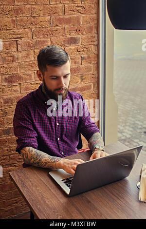 Un homme avec des bras tatoués de travailler avec un ordinateur portable. Banque D'Images
