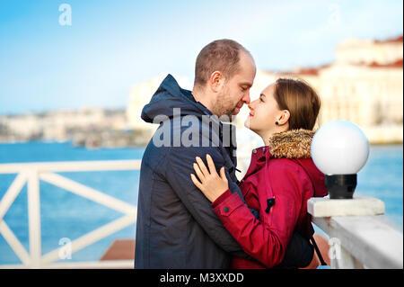 Vacances d'hiver, l'amour, de romance et de personnes concept - happy smiling young couple hugging outdoors Banque D'Images