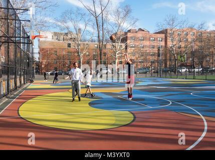 Les jeunes hommes jouant au basket-ball dans une aire à New York du Lower East Side Banque D'Images