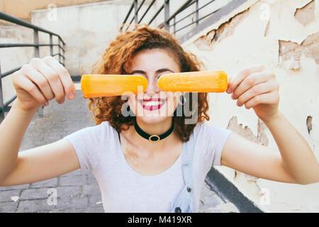 Jeune femme rousse de manger des glaces en été Banque D'Images