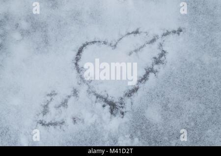 Le jour de la Saint-Valentin. Coeur percé par une flèche tracée sur la neige. Banque D'Images