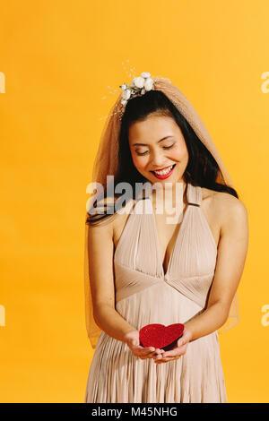 Asian bride en beige robe de mariage tenant un cœur rouge isolé sur orange Banque D'Images