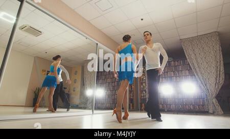 Beau jeune homme et femme danser et pratiquer la danse latine en costumes dans le studio Banque D'Images